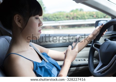 woman driver using a smart phone in car - stock photo