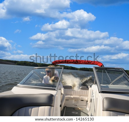Woman driving a jet boat on a lake in Kentucky, USA while holding her shih tzu puppy.