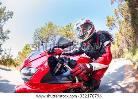 Woman driving a motorbike on a countryside road. Close up photo, the face of the woman is visible, there are some blurred trees on background. Transportation and speed concepts. - stock photo