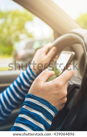 Woman driving car and texting message on smartphone, using mobile phone device while driving, dangerous and risky behavior in traffic - stock photo