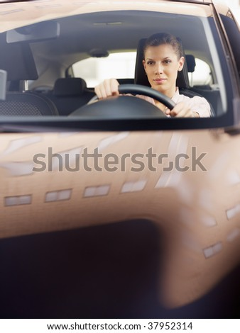 woman driving car. Reflections of building on hood. Copy space