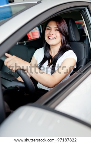 Woman driving her new car from the dealer - stock photo