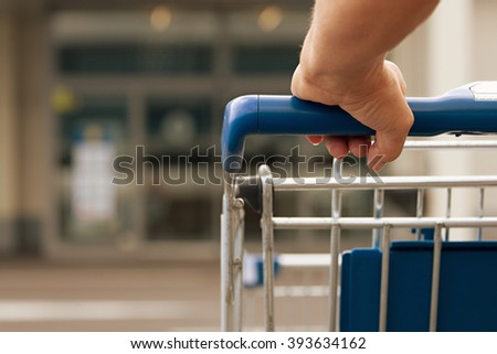 Woman driving shopping cart in front of the supermarket - stock photo