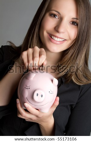 Woman dropping coin in piggy bank - stock photo