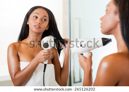 Woman drying hair. Rear view of beautiful young African woman washing hands in bathroom and looking at the mirror  - stock photo