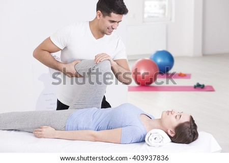 Woman during rehabilitation exercising with specialist in light interior