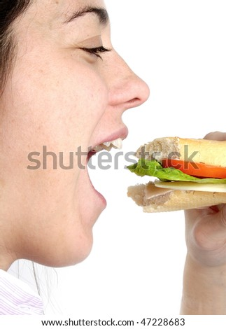 Woman eating a sandwich with lettuce, tomatoes, ham and cheese