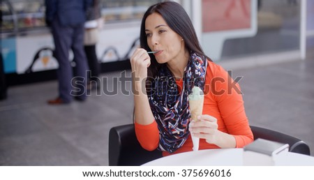 Woman eating an ice cream in a parlor or cafe - stock photo