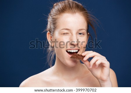Woman eating chocolate over blue backgorund
