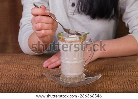 Woman eating dairy dessert spoon. The Dessert. Dessert based on milk and coffee. - stock photo