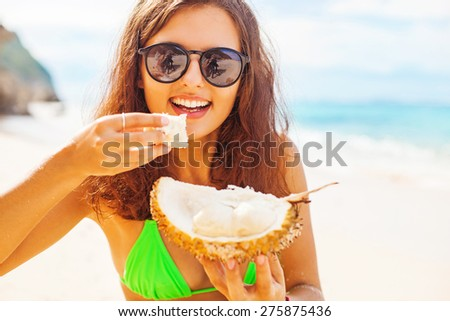 woman eating durian on a beach  - stock photo