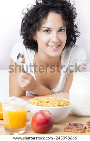 Woman eating healthy breakfast at morning on bed on white background. Smiling cute woman having breakfast of milk, cereals, orange juice. Woman is looking at camera. Concept of nutrition and diet. - stock photo