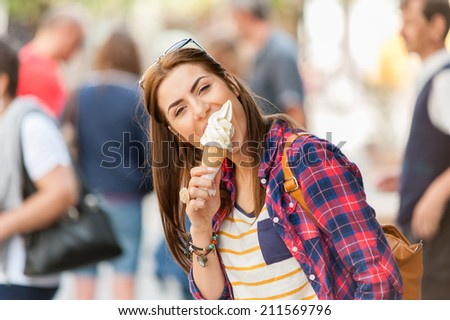 Woman eating Ice cream on vacation travel. Smiling girl having fun eating icecream outdoors during holidays in Europe.  - stock photo