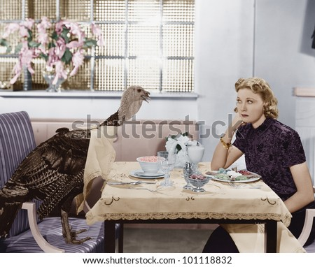 Woman eating meal at table with live turkey - stock photo
