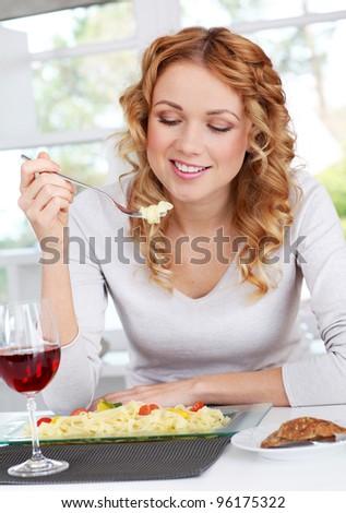 Woman eating pasta for dinner - stock photo