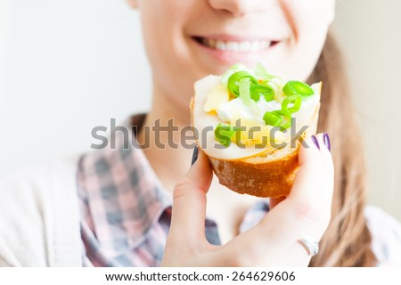 Woman eating sandwich with cheese and green vegetables  - stock photo