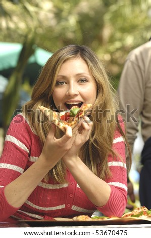 woman eating slice of pizza - stock photo