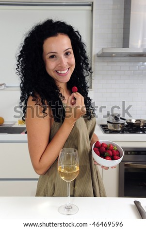 Woman eating strawberries and drinking wine - stock photo