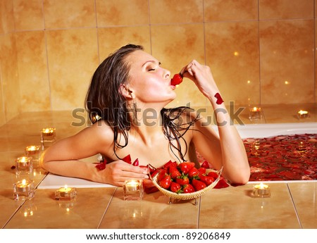 Woman eating strawberry in bathroom. - stock photo