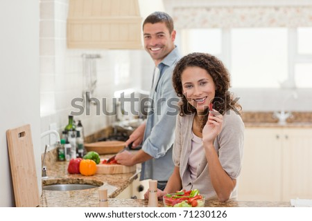 Woman eating while her husband is cooking at home - stock photo