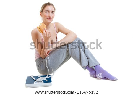 woman eats burger thinking about Weight loss - stock photo