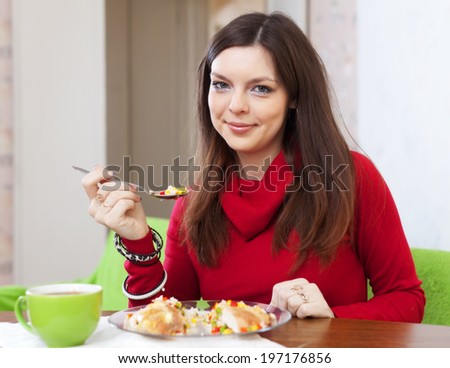 Woman eats chicken with rice and vegetables at home - stock photo