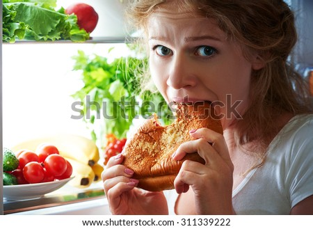 woman eats sweets at night to sneak in a refrigerator - stock photo
