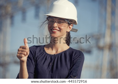 woman electrical engineer is giving thumbs up in front of power lines  - stock photo