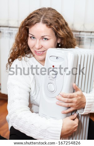 Woman embracing white oil heater sitting on the floor domestic room - stock photo