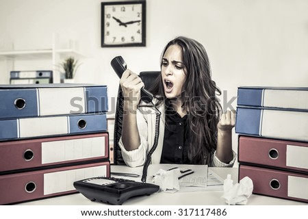 Woman employee yells on phone - stock photo