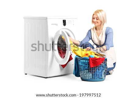 Woman emptying a washing machine isolated on white background - stock photo