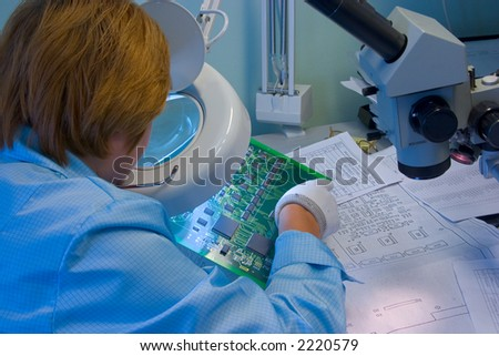 Woman engeneer inspecting computer mainboard though magnifying glass