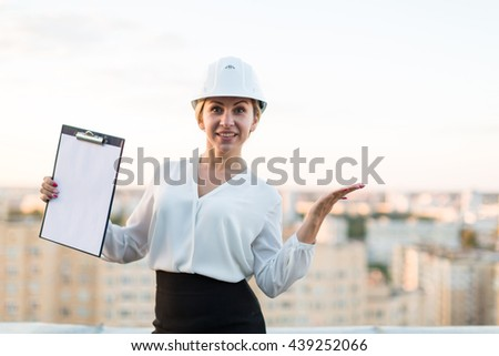 woman engineer in a helmet stands with a folder on the background of the city - stock photo