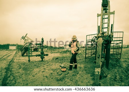 Woman engineer in the oil field talking on the radio wearing orange helmet and work clothes. Industrial site background. Toned.