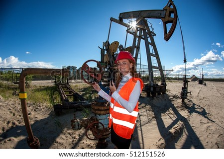 Woman engineer in the oil field talking on the radio wearing red helmet and orange work clothes. Industrial site background.