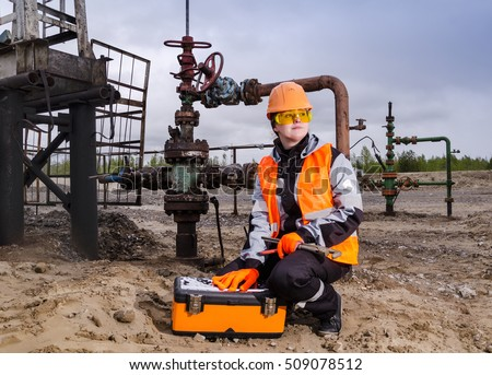 Woman engineer in the oilfield repairing wellhead with the wrench wearing orange helmet and work clothes. Oil and gas concept.