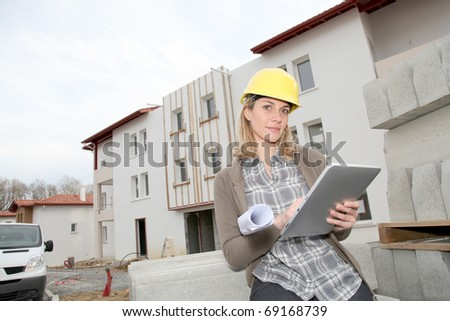 Woman engineer with security helmet standing on construction site - stock photo