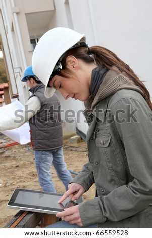 Woman engineer with white security helmet standing on construction site - stock photo