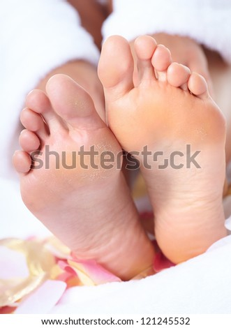 Woman enjoying a feet massage in a spa salon. - stock photo