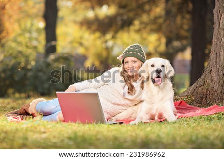 Woman enjoying a picnic with her dog in park in the autumn - stock photo
