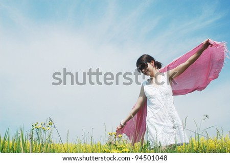 woman enjoying a sunny day on a field of spring flowers. - stock photo