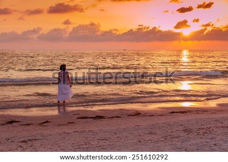 Woman enjoying beautiful sunset on the ocean, toned photo. - stock photo