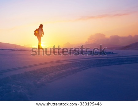 Woman enjoying beautiful sunset view from the high snowy mountain, discovering wild nature, active winter holidays