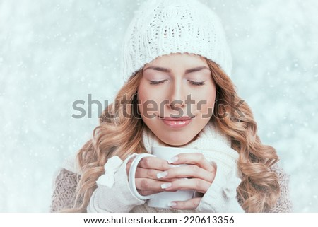 Woman enjoying big mug of hot drink during cold day.  - stock photo