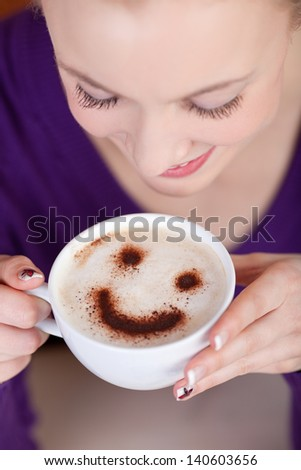 woman enjoying cappuccino with a smiley on foam - stock photo