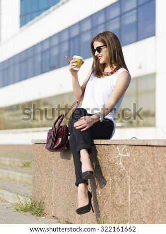 Woman enjoying coffee outside the office building - stock photo