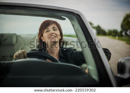Woman enjoying driving her convertible car - stock photo