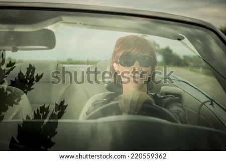 Woman enjoying driving her convertible car - stock photo