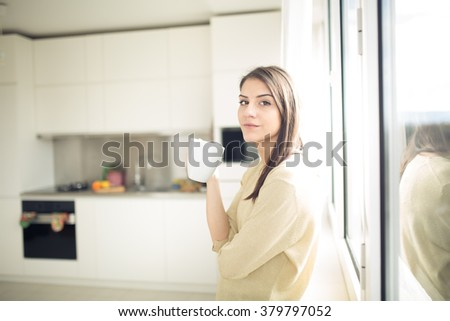 Woman enjoying,holding cup of hot beverage,coffee or tea.Enjoying her morning coffee in the kitchen.Savoring a cup of coffee in bliss and appreciation.Looking trough the window.Emotional.Thinking - stock photo