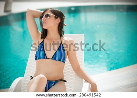 Woman enjoying in after procedures.Sexy beautiful brunette woman with in bikini relaxing beside a swimming pool in summer on tropic island.Woman relaxing in deck chair.Sunscreen,protection,summer body - stock photo